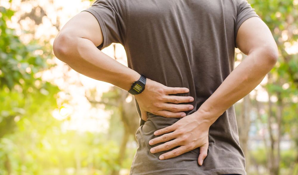 man outside holding his back because of lower back pain
