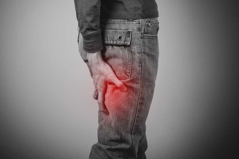man with sciatica pain holding the back of his leg with
